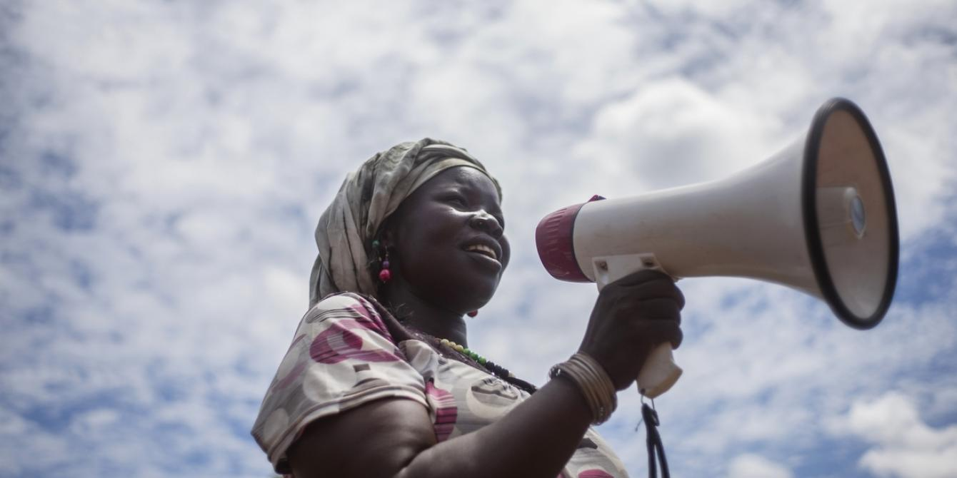 Sarah, the chairperson of a handicrafts group in Bidibidi refugee setttlement, uses a microphone to call women to join her group. Photo:Kieran Doherty/Oxfam